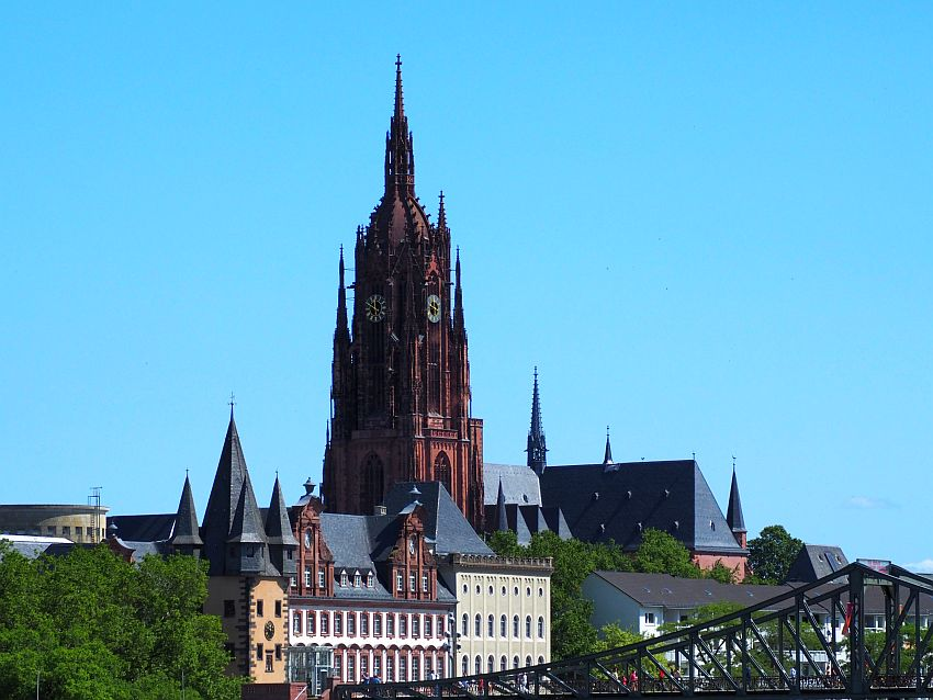 The cathedral tower is dark red stone, with pointed towers on four corners and at several heights, and with a very long narrow point on top. It has large clocks about halfway up, 2 of which are visible in this photo. In front of it, lower buildings line the river, and an iron bridge crosses the bottom of the photo.
