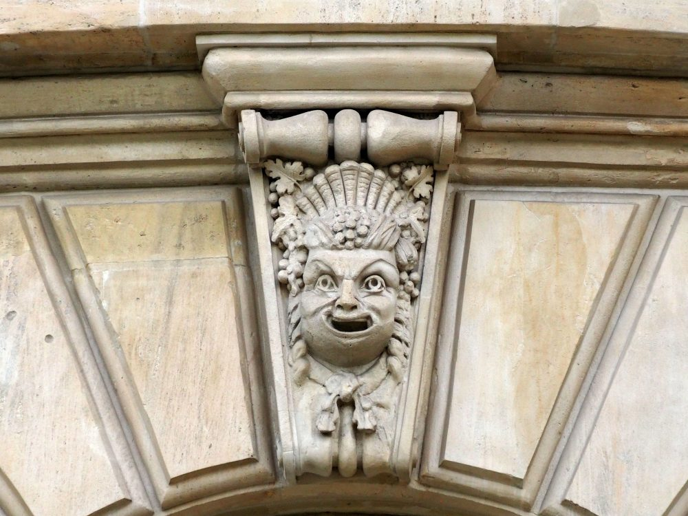 A face smiles comically, wearing an odd headress and curls down the sides.