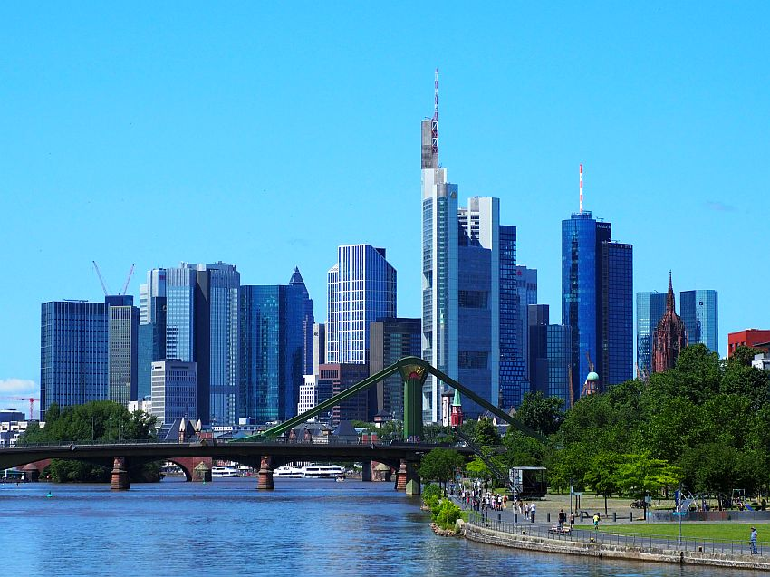 The Frankfurt skyline: a cluster of tall buildings of various shapes and sizes against a clear blue sky. In the foreground, the river, and a green metal bridge crossing across the bottom of the photo.