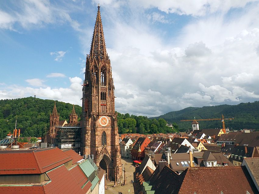 In the middle is the spire of the cathedral, all lacy gothic arches. Around it are much lower buildings around an open space - the Munsterplatz. In the background, low green hills.
