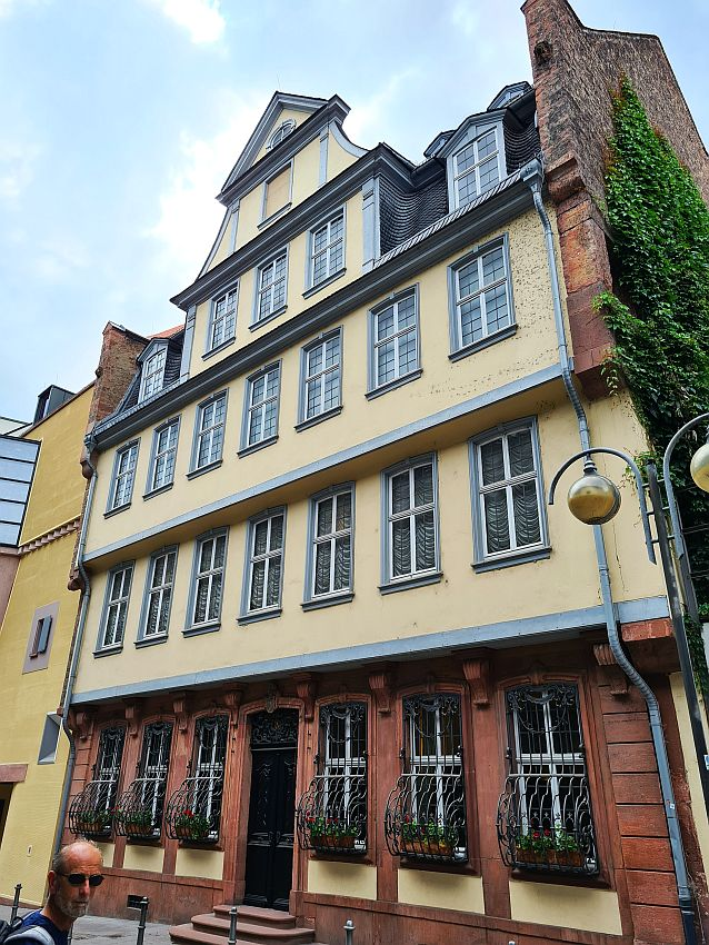 Four or five stories high, each story extends out by a foot or two beyond the story below it. It's a row house, so the sides are not visible. The ground floor is dark red stone. The floors above are plastered and painted light yellow, while the trim is grayish blue.