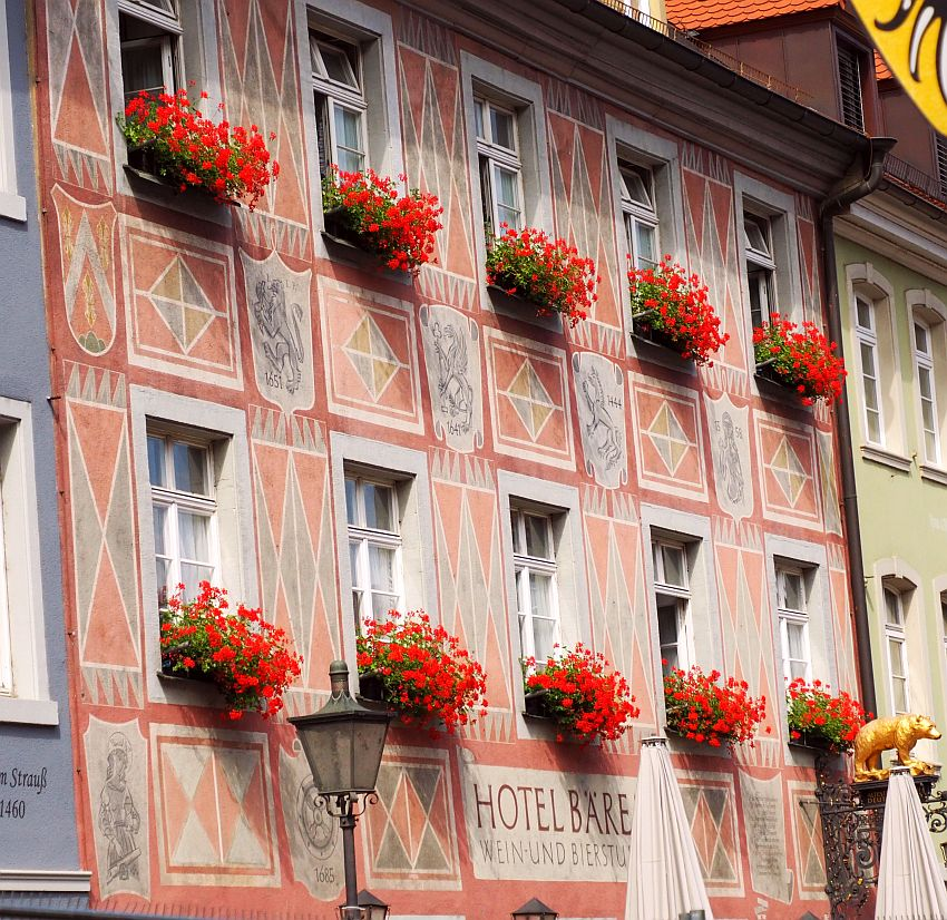 The building is flat-fronted, covered with painted plaster. The paint is pale red and light blues and is geometric patterns between the rows of windows. Between the 2 floors that are visible in this photo are images which seem to be coats of arms. Under very window - 5 above and 5 below - is a window box with bright red geraniums.