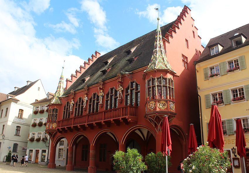 The building is painted red. It has a steep roof and step gables on either side. The ground floor has a row of pillars with arches between them, making a portico along the front of the building. The floor above that has 5 large arched windows with a narrow balcony in front of them, and at either corner of the building is a round turret with a pointed roof.