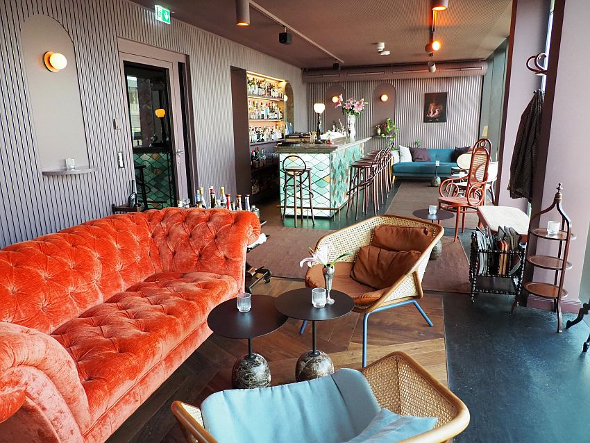 In the background is the bar with bar stools lined up along it. In the foreground, an orang sofa that appears to be upholstered in velvet and two ratan chairs opposite it with cushions. Other such chairs are visible along the wall and another sofa, blue this time, beyond the bar in the background. Coffee tables, a magazine rack, a coat tree, etc. make it look very homey.