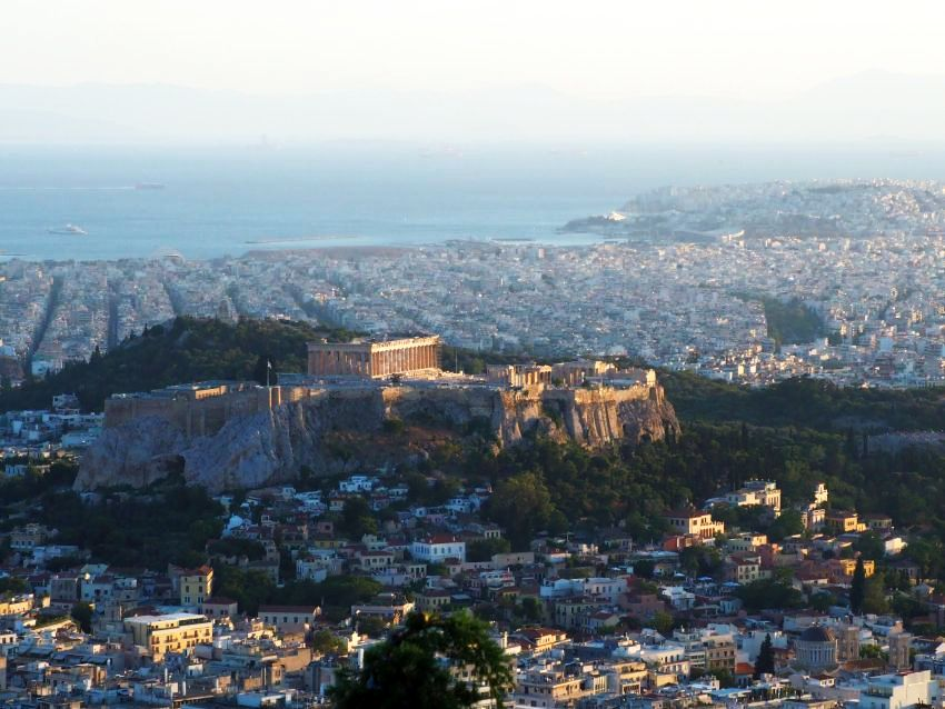 A view over Athens shows lots of white buildings, densely packed, on mostly flat ground, with the sea in the background (dim because of the haze). In the middle, a large hill, green around its edges but cliffs within that, and the acropolis and other ruins visible perched on the cliffs.