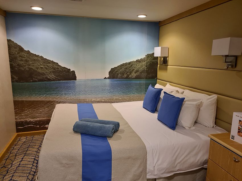 This room on the Celestyal Crystal is square and is filled mostly with a queen-sized bed  extending out from the right-hand wall and a nightstand beside it. The back wall has a photo that covers the entire wall showing a beach in the foreground, a bay, and two hills jutting out from the left and the right to the opening of the bay.