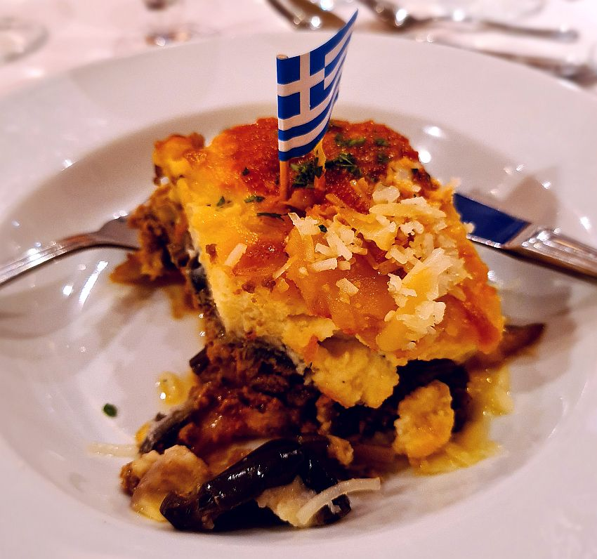 A square of moussaka with a little blue and white Greek flag on a toothpick in the middle.