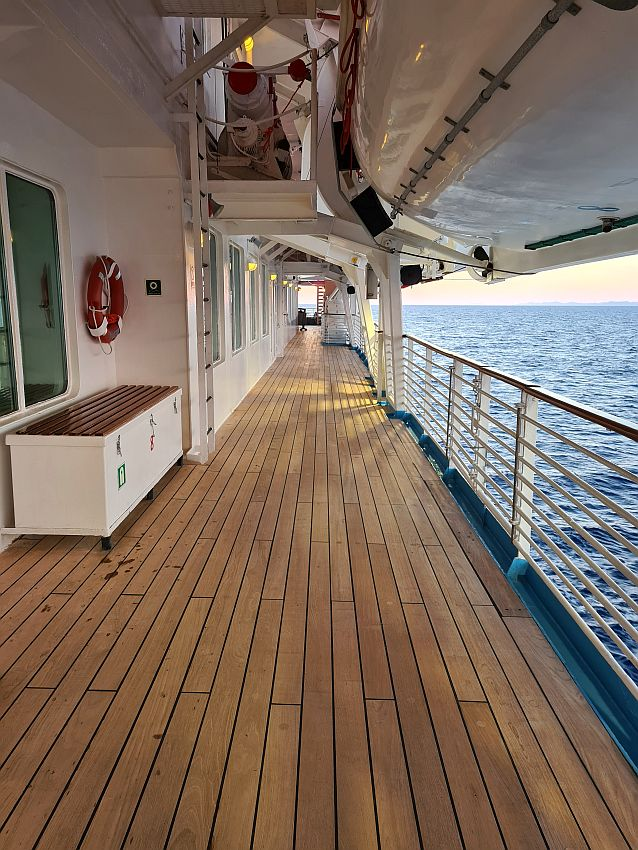Looking down the long, narrow promenade. Wooden flooring, the rail on the right, the bottoms of lifeboats above.