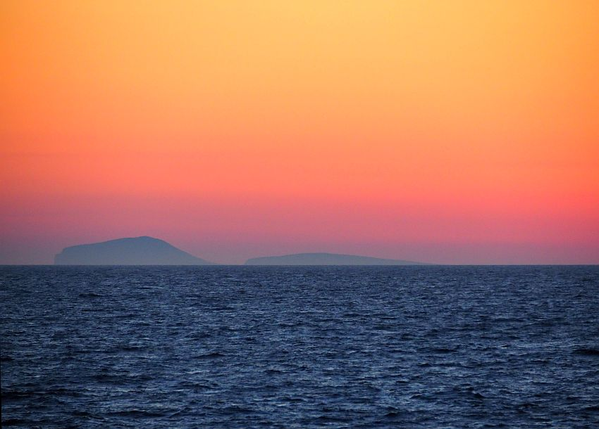 The sky just after the sun is fully down: a few low hills in the distance. Dark sea, then shades of red near the horizon, lightening to orange above.