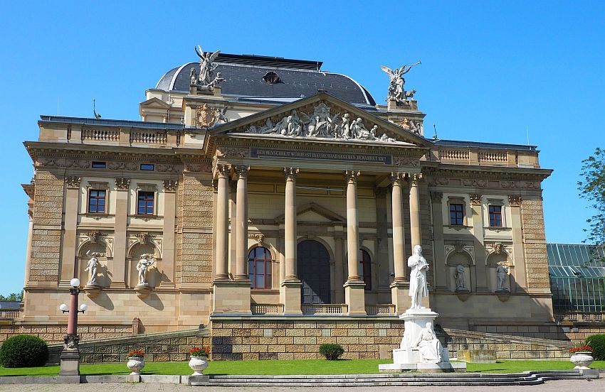 A neo-classical facade, with a center pediment held up by tal pillars. Baroque bas-relief in the pediment, large statues of angels blowing trumpets on each corner above the pediment. Statues in window-sized niches on the lowest story too. In front, a statue of Schiller on a tall pedestal. Typical of the European Thermal Towns.