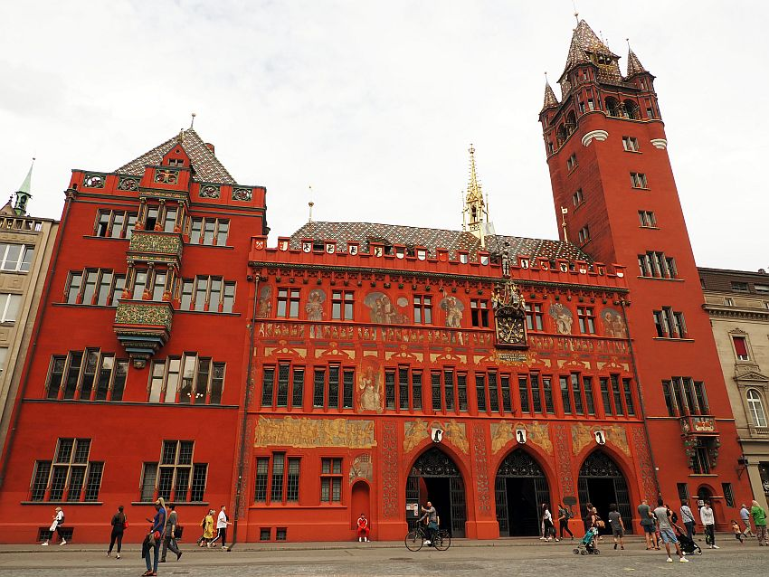 One of the best known of the Basel sights, the Rathaus is painted bright red. It has three gothic arches on the ground floor for its entrance while the rest of the windows are all simple but very narrow rectangles. The left side of the building has the center windows on the upper stories extending outwards like bay windows. The right sid of the building has a tall tower, with fanciful turrets at the top. The building has decorative elements - paintings and sculptures - across the middle, and the roof is colorfully tiled.