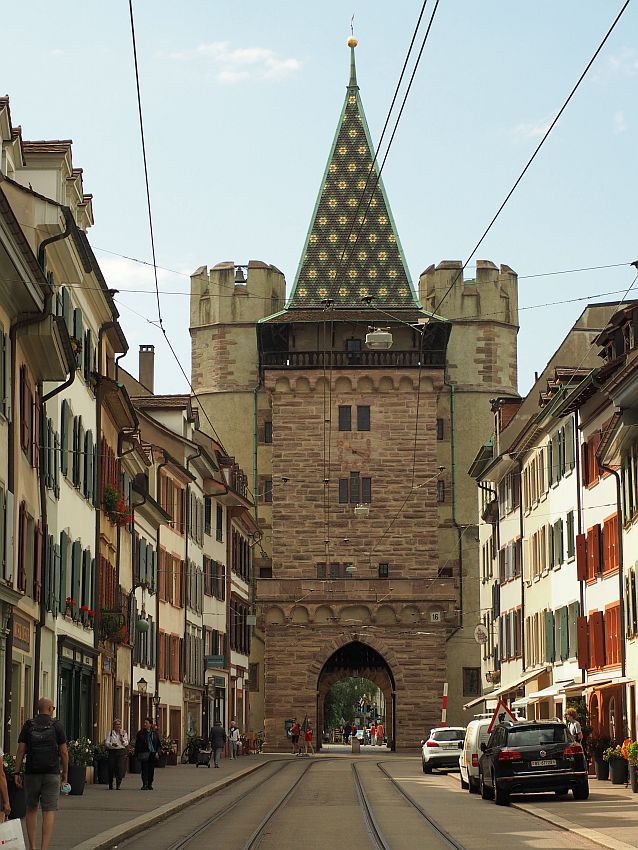Looking down a street with buildings on either side (white with rows of windows, each with shutters open). At the end of the road, the gate is large, several stories taller than the buildins and blocking the entire road. The tower has an archway at the road level to the other side. The tower is made of stone blocks and has just a few windows on each level. The roof is very steep and pointed and covered in green tile with yellow flowers. On either side of the tower are two more towers, somewhat shorter; they are cylindrical with crenellations at the top.