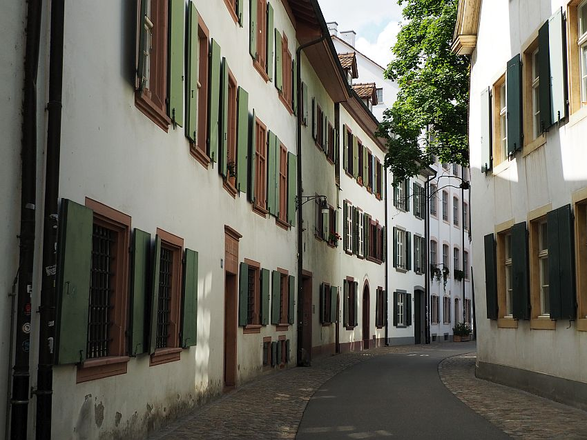 Looking down a road that curves to the right out of sight. The buildings also seem to curve. They are all white and have lots of windows, each with open green shutters.