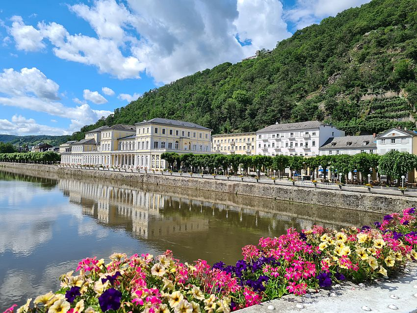 View from above the river: the building is right along the river, three stories high, with columns on the ground floor and lots of windows on all floors. It is light yellow with white trim. Behind it is a row of other buildings, also light yellow or white. Behind that, a tree-covered hill. In the foreground, brightly colored flowers in boxes along the edge of the bridge.