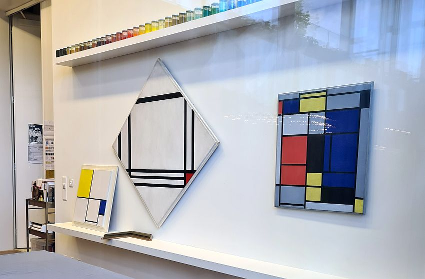 Three Mondrians, all with the typical simple black lines and grids, and some red, yellow, blue or black filled-in rectangles. Above them is a shelf holding a neat line of bottles in a range of colors, presumably paints.