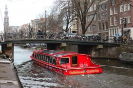 A bright red canal tour boat passes under a bridge.