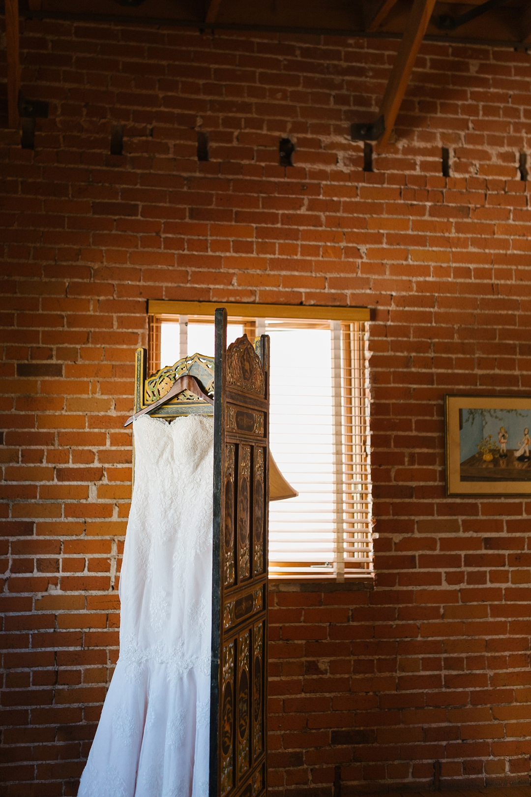 wedding gown hangs against brick wall at Carondelet House