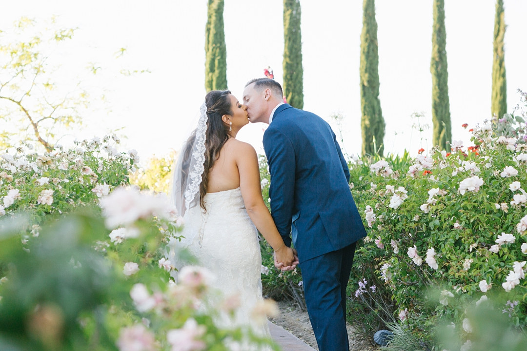 bride and groom kiss surrounded by flowers at gershon bachus vintners