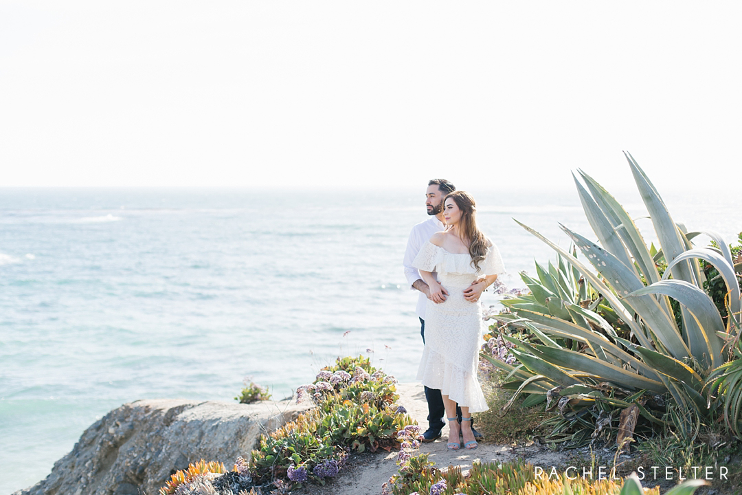 couple looks out over ocean at laguna beach engagement session