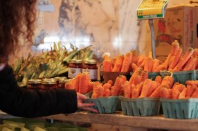 A customer picking out the best box of fresh carrots at an indoor farmers market