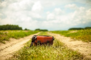Red purse sitting on dirt road surrounded by grass.