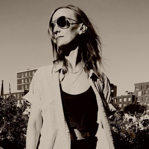 Black and white photo of Rachel Velebny, from the waist up, with her head turned to the side. Her hair is down, she's wearing sunglasses, and a cropped shirt with an unbuttoned, oversized short-sleeve shirt on top. There are flowers in the near background and brick buildings in the far background.