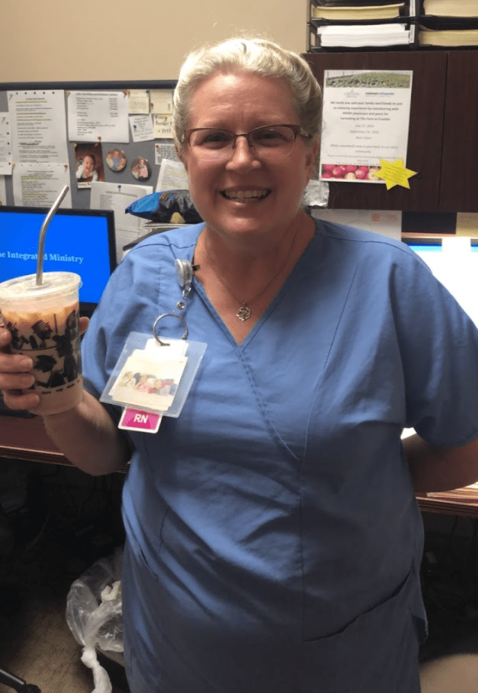 Sue Biddle smiles with her coffee in her hand