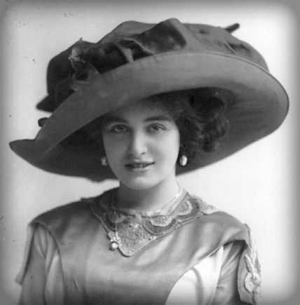 bust of Edwardian woman in giant sized round hat with twelve-inch wide satin bow