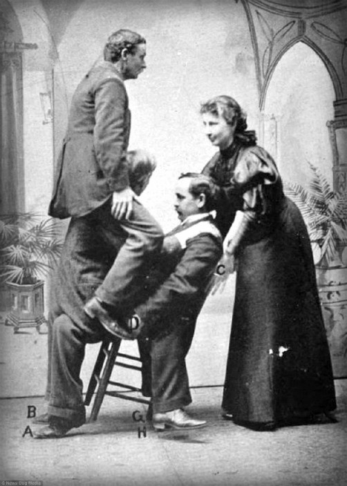 Victorian Georgia Wonders: 1897 Black and white photo of Lulu Hurst in dress lifting two men on chair.