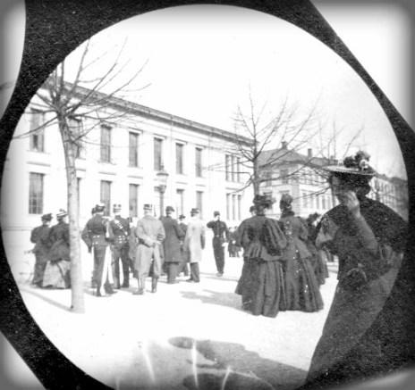 Victorian Era Spy Camera: black and white photo of a dozen people men and women walking on street. Image: wiki-visually.