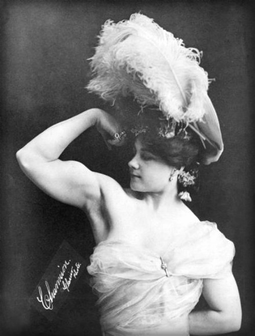 Victorian Strongwomen Charmion in front view wears Victorian hat with large feathers while she flexes her right bicep.. Image: Wikipedia.