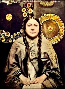 Waist up, seated, photograph of Mary Baldwin Bottineau, 1914 in braids and Native American robe. Image: Library of Congress.