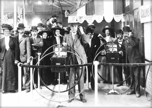 Black and White photo of man in suit demonstrating early phone, 1888 and surrounded by crowd of about twelve people all dressed in suits and long dresses.