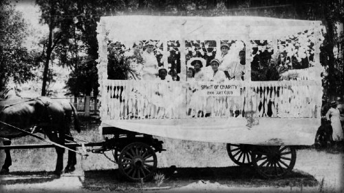 six African American women and two African American girls on the float. There is a sign on the float that reads, 'The Spirit of Charity 1906 Art Club.' The float is hitched to two horses