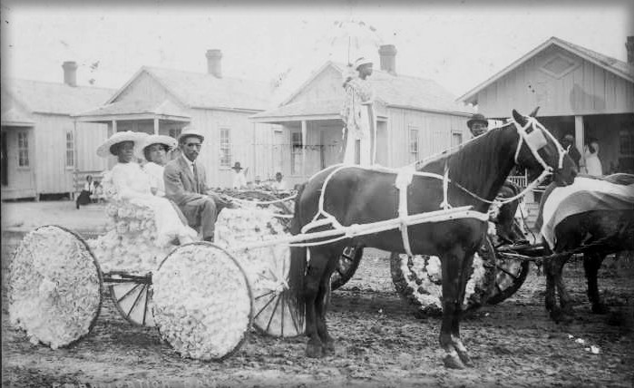 1913 Photograph of Two Black American Women dressed in white dresses and hats and One Black American Man Driving a Small horse-drawn carriage decorated with flowers.