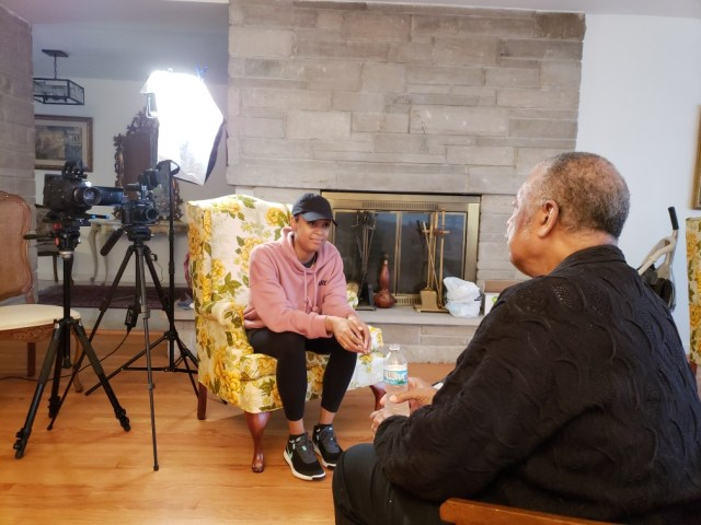 Filming of a Black woman interviewing a an older, Black male in a living room.