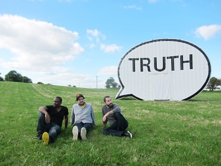 """The three founders of """"In Search of the Truth"""" sit in a grassy field in Ireland near their inflatable creation."""