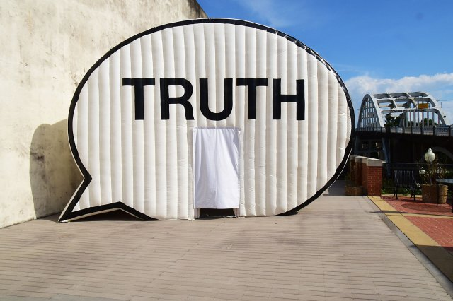 The Truth Booth Text Balloon Tent sits in an urban area near a bridge
