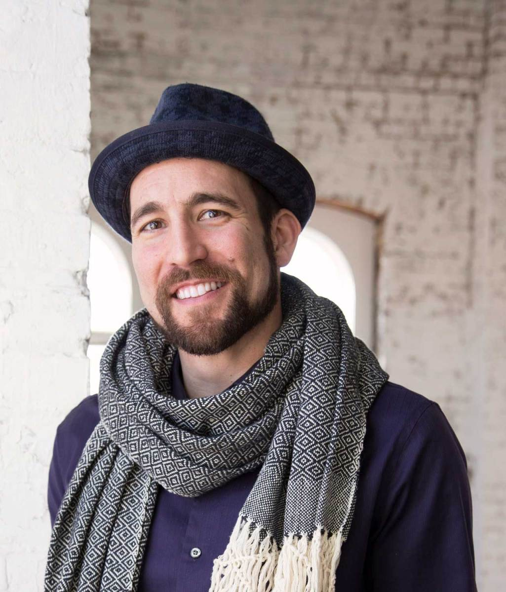 Photo of the artist Jacob Stanley in a cap and scarf