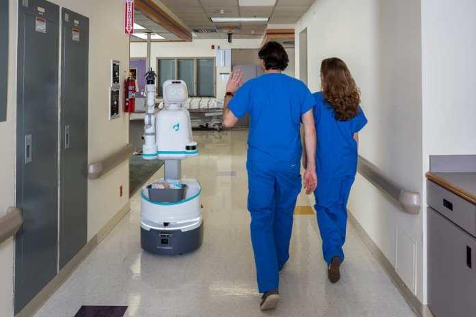 """Enfermagem no futuro: Imagem mostra dois profissionais """"comprimentando"""" um robô em um hospital"""