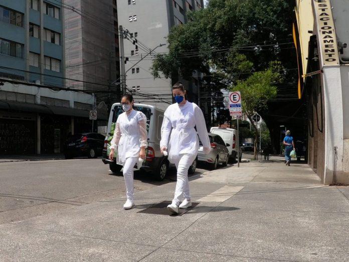 Conversas sobre o futuro: duas profissionais da saúde, de máscara, caminham em uma rua vazia de são paulo - foto: fotos públicas