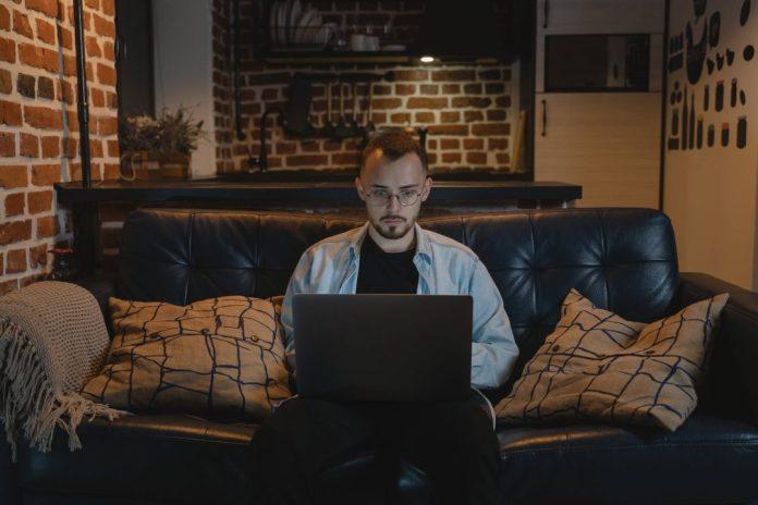 no futuro das empresas de TI o home office tende a se consolidar man in black crew neck t shirt using black laptop computer