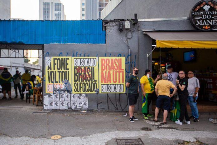 foto Felipe Campos Melo Notas econômicas: grupo de apoiadores de bolsonaro conversa diante de bar e ao lado de faixas que protestam contra o governo