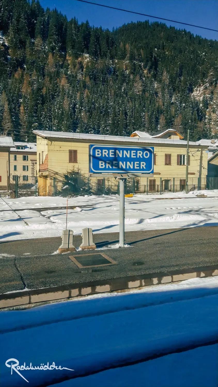 Bahnhofsschild aus dem Zugfenster mit schnee