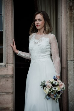Bride looking out from doorway at Askham Hall