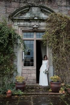 Bride looking down at her flowers in doorway of Askham Hall, Eden Valley