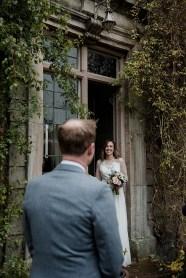 Looking over the shoulder of groom to the bride in doorway of Askham Hall
