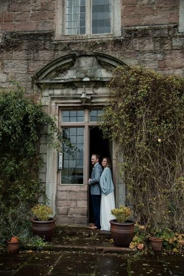 Bride and Groom in romantic pose in doorway of Askham Hall, Cumbria