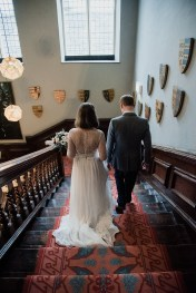 Bride and Groom walking down grand staircase at Askham Hall, Cumbria