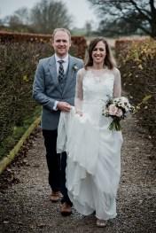 Groom carrying brides dress as the walk along path at Askham Hall